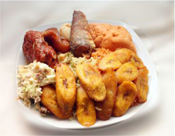A dish of fried and jollof rice garnished with plantain